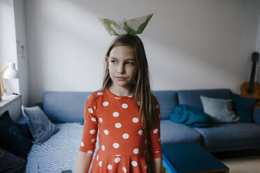 Girl balancing paper boat on her head at home - KNSF05877