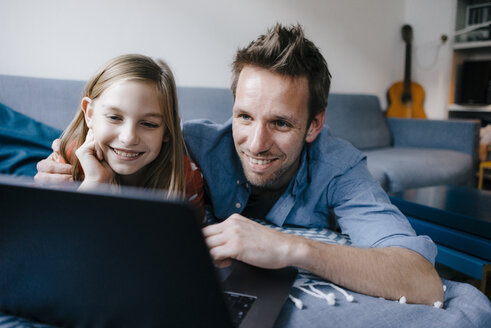 Happy father and daughter lying on couch at home using laptop - KNSF05886