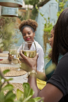 Woman sitting in a restaurant with her friends drinking white wine - VEGF00164