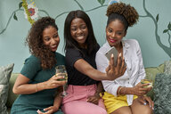 Portrait of three happy friends taking selfie with smartphone - VEGF00167