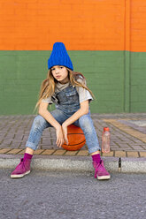 Young girl sitting on basketball - ERRF01243