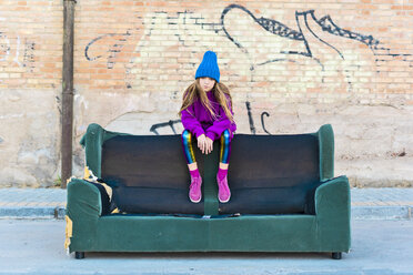Girl wearing colorful clothing and sitting on a couch outdoors - ERRF01258