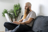 Hipster sitting on couch at home using laptop - AFVF02932