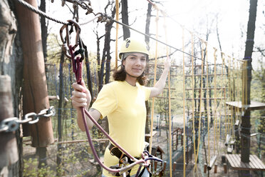 Young woman wearing yellow t-shirt and helmet in a rope course - EYAF00197