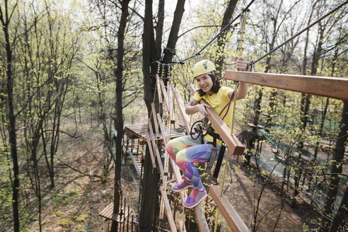 Russia, Moscow, young smiling woman in yellow t-shirt, yellow helmet and rainbow pants in rope park - EYAF00203