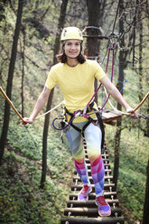 Young woman wearing yellow t-shirt and helmet and rainbow pants in a rope course - EYAF00206