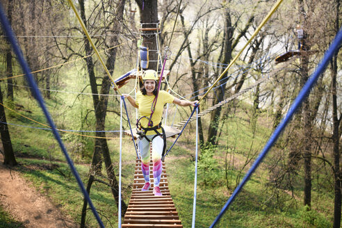 Russia, Moscow, young smiling woman in yellow t-shirt, yellow helmet and rainbow pants in rope park - EYAF00209