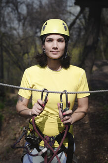 Young woman wearing yellow t-shirt and helmet in a rope course - EYAF00212