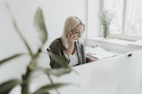 Young woman talking on cell phone at desk in office - AHSF00299