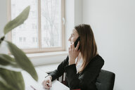 Young woman talking on cell phone at desk in office - AHSF00305