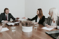Businesswoman handing over paper to colleague during a meeting in conference room - AHSF00311