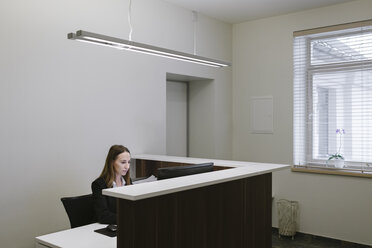 Young woman working at the reception desk in office - AHSF00314