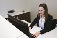 Young woman working at the reception desk in office - AHSF00317