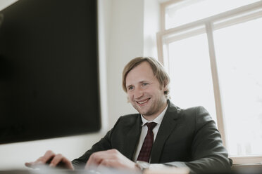 Smiling businessman using computer at desk in office - AHSF00323