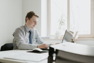 Young businessman using laptop at desk in office - AHSF00326