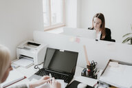Two young women working at desk in office - AHSF00332