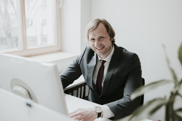 Portrait of smiling businessman using computer at desk in office - AHSF00344
