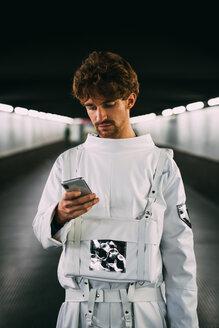 Astronaut using smartphone on covered bridge - CUF50682