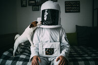 Pet dog licking astronaut on bed - CUF50694