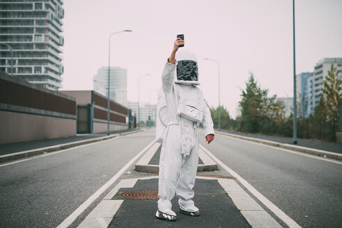 Astronaut taking selfie in middle of road - CUF50703