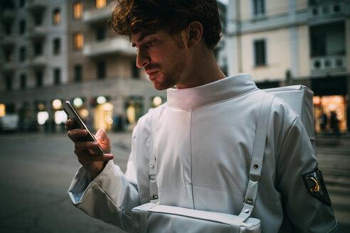 Astronaut using smartphone on pedestrian crossing - CUF50706