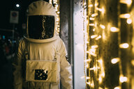 Astronaut standing in front of illuminated shopfront - CUF50718