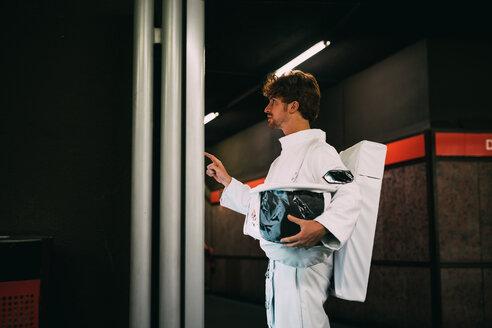Astronaut reading signboard in train platform - CUF50721