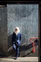 Senior businessman leaning against building wall - CUF50736