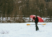 Male kayaker carrying kayak over his shoulder in snow, Domodossola, Piemonte, Italy - CUF50763
