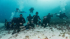 Underwater view with group shot of divers on ocean seabed in Raja Ampat, Sorong, Nusa Tenggara Barat, Indonesia - CUF50796