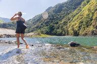 Woman crossing stream, Pagudpud, Ilocos Norte, Philippines - CUF50874