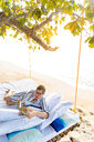 Woman reading book on swing bed in beach, Ginto island, Linapacan, Philippines - CUF51012