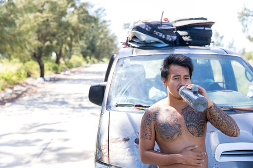 Man drinking in front of vehicle parked on road, Pagudpud, Ilocos Norte, Philippines - CUF51027