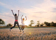 Girlfriends jumping in field, Southwold, Suffolk, United Kingdom - CUF51036