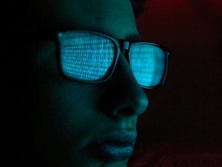 Cyber Crime, reflection in spectacles of virus hacking a computer, close up of face - CUF51045