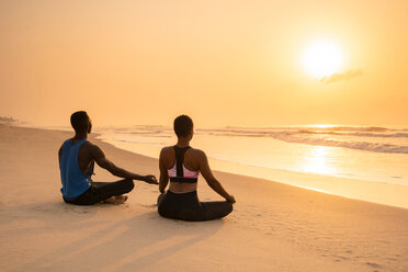 Couple practising yoga on beach - CUF51063
