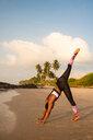 Woman practising yoga on beach - CUF51066