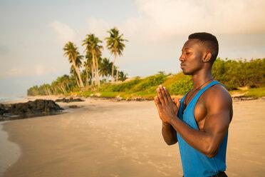 Man practising yoga on beach - CUF51069
