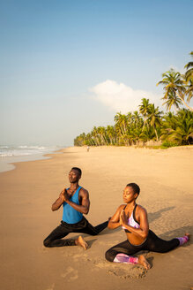 Couple practising yoga on beach - CUF51072
