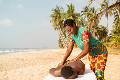 Woman massaging man on beach - CUF51075