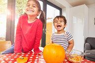 Children carving pumpkin in kitchen - CUF51087