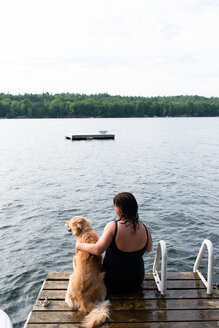 Woman with dog looking out from lake pier, rear view, Kingston, Ontario, Canada - ISF21303