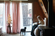 Woman drinking on sofa with dog at home - ISF21324