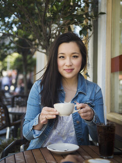 Smiling Chinese woman drinking coffee at outdoor cafe - BLEF03065