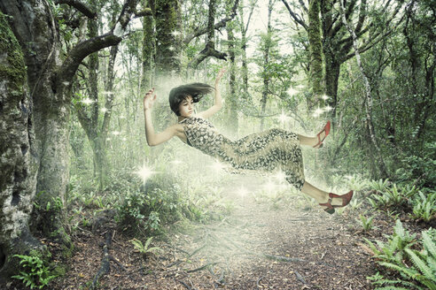 Mixed Race girl floating in forest - BLEF03086