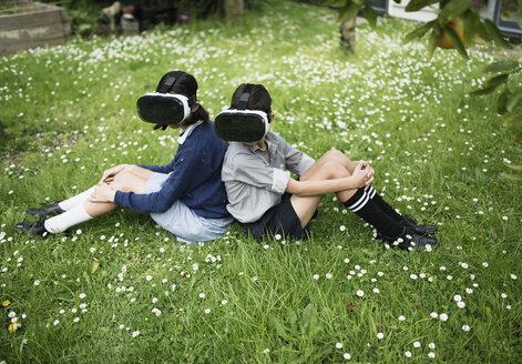 Mixed Race brother and sister sitting in grass wearing virtual reality goggles - BLEF03104