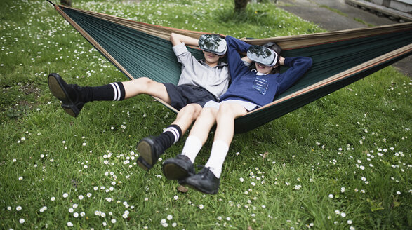 Mixed Race brother and sister in hammock wearing virtual reality goggles - BLEF03107