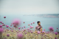 Caucasian man sitting in field of flowers near ocean - BLEF03122