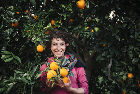 Smiling Caucasian woman holding oranges under tree - BLEF03152