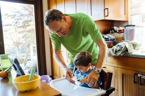 Father wiping hands of son in highchair - BLEF03182